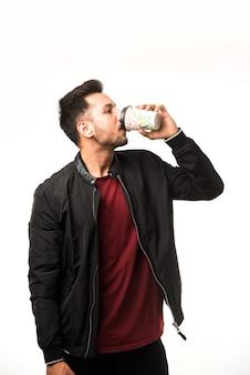 Indiase aziatische jongeman met papieren koffiekopje met een zwarte plastic dop geïsoleerd op een witte achtergrond in de studio, reclame voor koffie