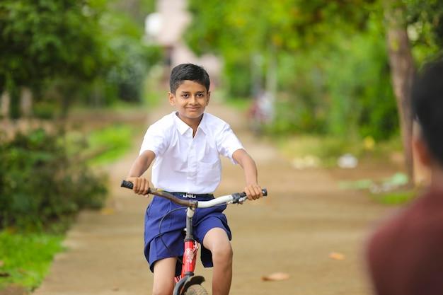 Indiase / aziatische kleine jongen geniet van fietsen