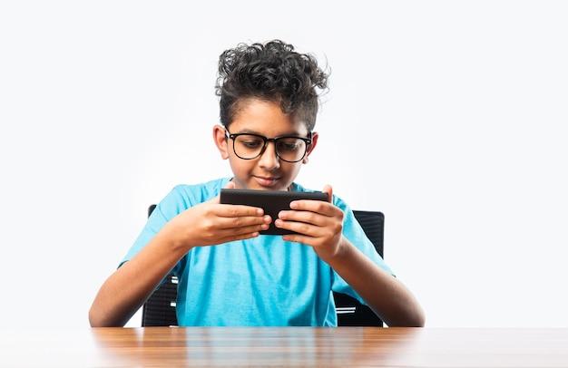 Indiase aziatische kleine jongen of kind die smartphone gebruikt voor gamen of voor onderwijs