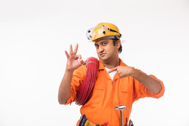 Indiase aziatische knappe elektricien of ingenieur in actie met gele veiligheidshoed geïsoleerd