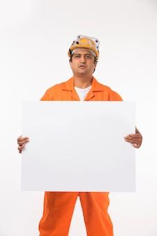 Indiase aziatische knappe elektricien of ingenieur in actie met gele veiligheidshoed geïsoleerd Premium Foto