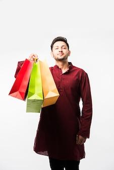 Indiase aziatische man in etnische slijtage met boodschappentassen, staande geïsoleerd op witte achtergrond