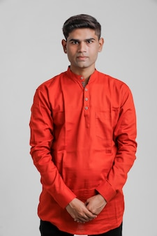 Indiase / aziatische man in rood shirt en permanent over wit