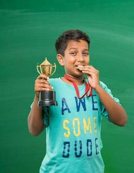 Indiase aziatische schoolkinderen die gouden trofeekop houden over groene schoolbordachtergrond
