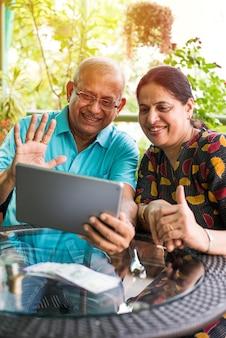 Indiase aziatische senior paar videochatten op tabletcomputer zittend op de bank of in de tuin thuis, selectieve focus