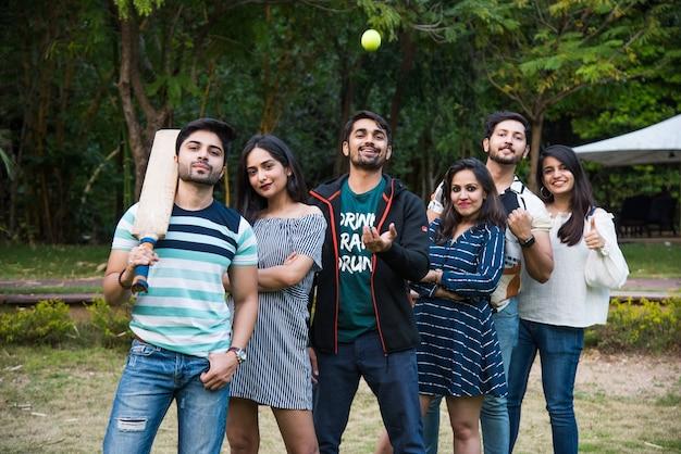 Indiase aziatische universiteitsvrienden poseren met cricketbat en -bal uitdagend of poseren voor een foto