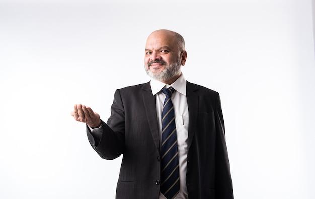 Indiase aziatische zakenman van middelbare leeftijd met baard die elegant zwart pak draagt en met hand en vinger wijst. presentatie van product, dienst of kopie ruimte