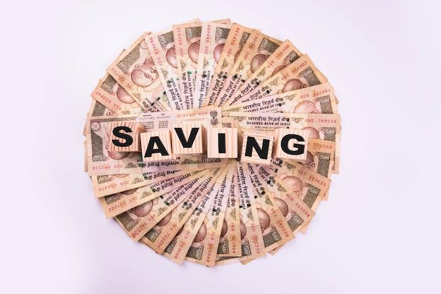 Indiase bankbiljetten gerangschikt in cirkelvorm en tekstbudget of besparing geschreven op houten blokken, op witte achtergrond