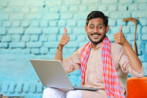Indiase boer die laptop gebruikt en thuis dreunt.