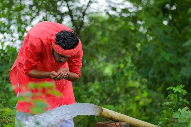 Indiase boer drinkwater met hand uit pijpleiding op veld