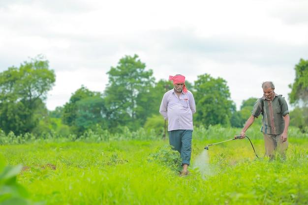 Indiase boer en arbeid sproeien van pesticiden op het veld