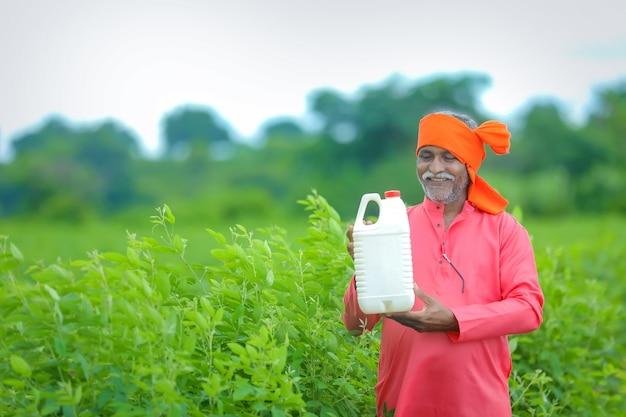 Indiase boer kunstmest fles tonen op veld