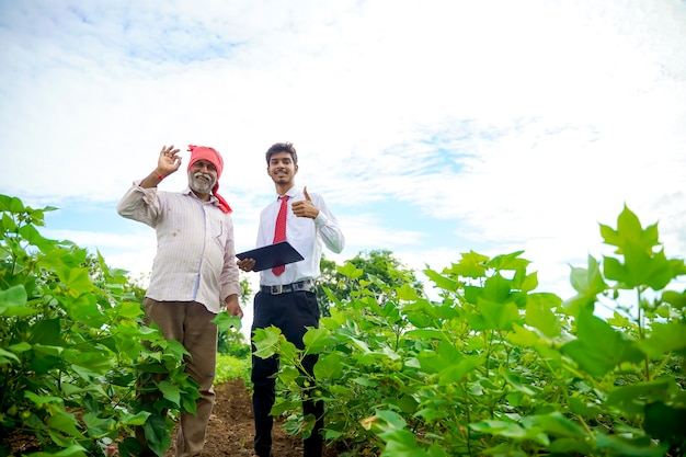 Indiase boer met agronoom op katoenveld, duimen opdagen