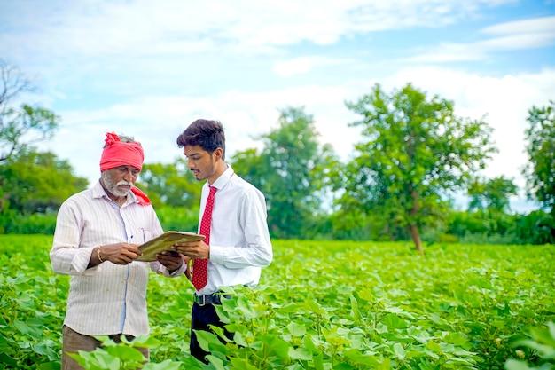 Indiase boer met agronoom op katoenveld en agronoom die wat informatie schrijft op het letterblok