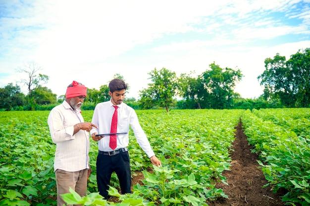 Indiase boer met agronoom op katoenveld, met wat informatie op tabblad