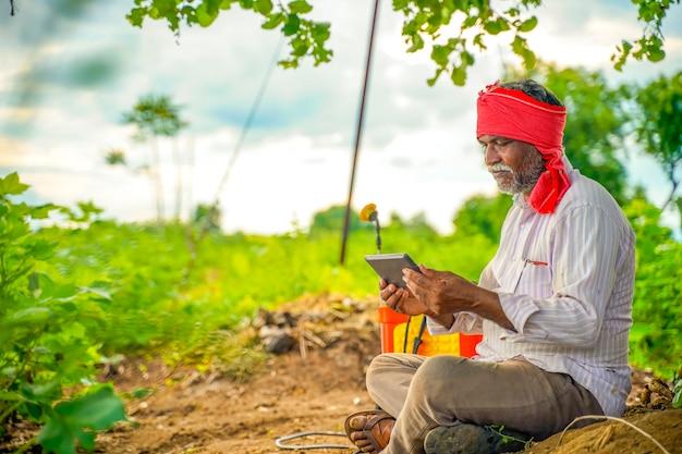 Indiase boer met behulp van mobiele telefoon op landbouwgebied