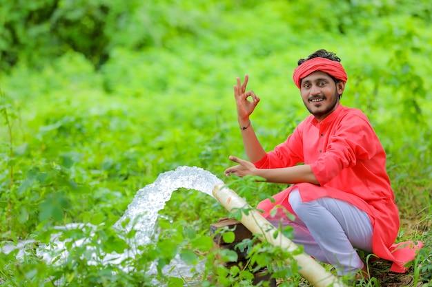 Indiase boer met waterstroom uit pijp op veld