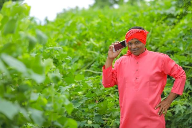 Indiase boer praten op mobiele telefoon op landbouwgebied