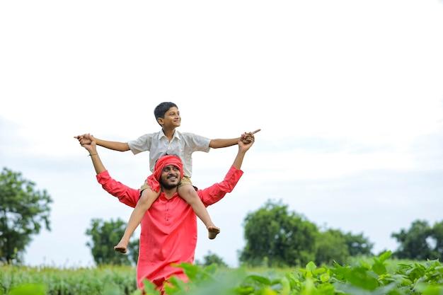 Indiase boer speelt met zijn kind op groen veld