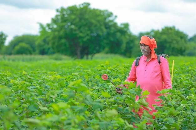 Indiase boer sproeien van pesticiden op katoenveld