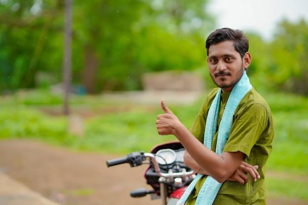 Indiase boer zit op de fiets en laat klappen zien