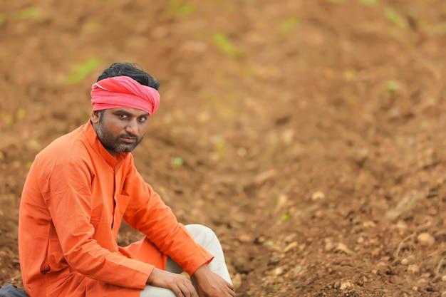 Indiase boer zit op landbouwveld