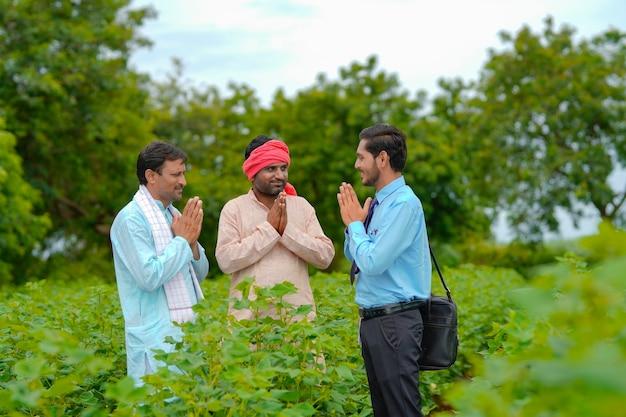 Indiase boeren en agronoom die namaste of welkom gebaar geven op landbouwgebied.