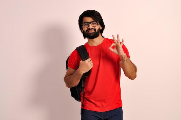Indiase collage gaan man met rugzak lachende student in brillen ok teken met hand tonen