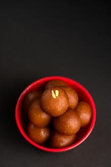 Indiase dessert of zoete schotel gulab jamun in een kom op donker.