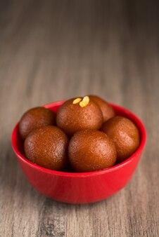 Indiase dessert of zoete schotel gulab jamun in een kom op houten.
