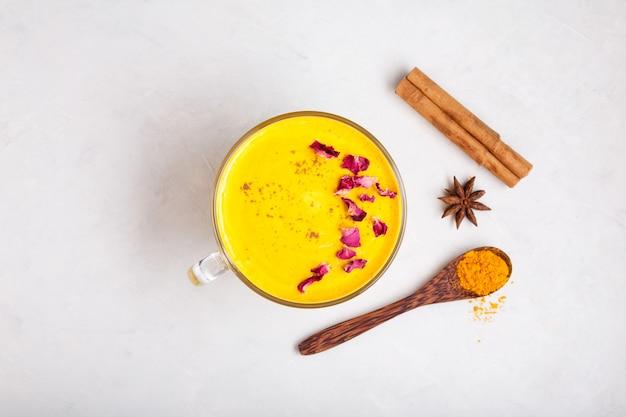 Indiase drank golden milk of kurkuma latte versierd met rozenblaadjes trendy aziatische drank