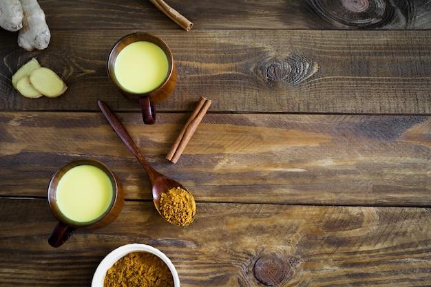 Indiase drink gouden melk in twee houten bekers met ingrediënten gember, kurkuma op een houten lepel en kaneelstokjes bovenaanzicht op een houten achtergrond met kopie ruimte.