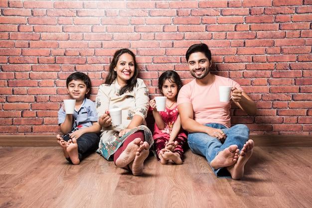 Indiase familie consumptiemelk wit zittend op houten vloer tegen rode bakstenen muur binnenshuis