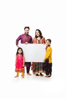 Indiase familie die diwali viert terwijl ze een leeg wit bord of plakkaat vasthoudt. staan geïsoleerd op een witte achtergrond en kijken naar de camera