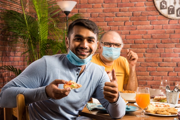 Indiase familie en vrienden dragen gezichtsmasker tijdens het eten in restaurant na corona pandemie ontgrendelingsconcept met nieuwe normale levensstijl in india