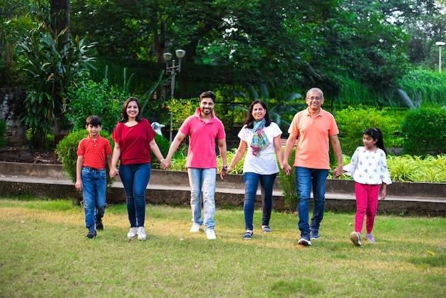 Indiase familie geniet van picknick - aziatische familie van meerdere generaties die loopt of een achtervolgingsspel speelt in het park en een menselijke ketting maakt. selectieve focus