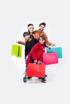 Indiase familie met boodschappentassen in winterkleding of warme kleding tegen de achtergrond