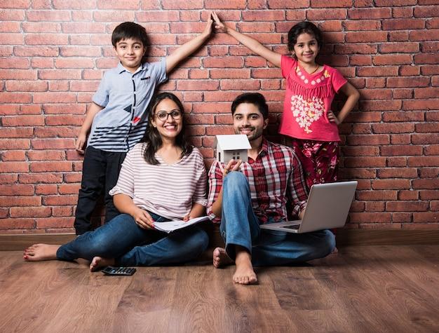 Indiase familie vader moeder zoon en dochter met 3d-papieren model van huis real istate concept in india