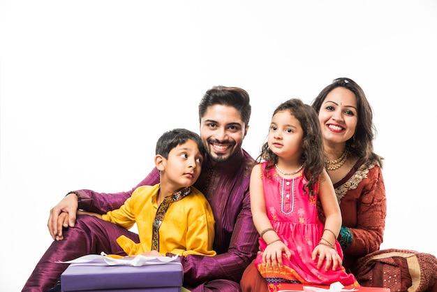 Indiase familie viert diwali of deepavali in traditionele slijtage zittend geïsoleerd op een witte achtergrond met geschenkdozen en lamp in thali