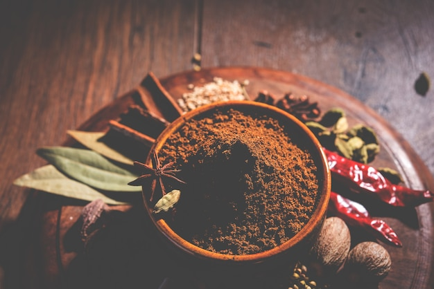 Indiase garam masala poeder in kom en het is ingrediënten kleurrijke kruiden. geserveerd op humeurige achtergrond. selectieve focus