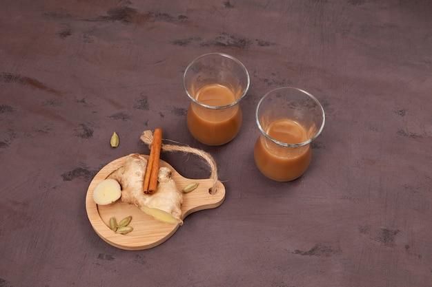 Indiase gemberthee met melk en kruiden op bruin