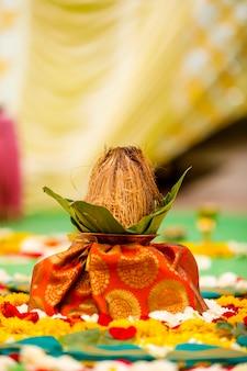 Indiase huwelijksceremonie: decoratieve coper kalash met groen blad en kokos