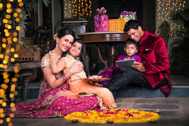 Indiase jonge familie die bloem rangoli maakt of diya's schikt voor diwali-festivalnacht op de veranda met geschenken en bokeh op de achtergrond