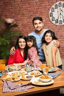 Indiase jonge familie van vier eten aan de eettafel thuis of in het restaurant. zuid-aziatische moeder, vader en twee dochters die samen eten