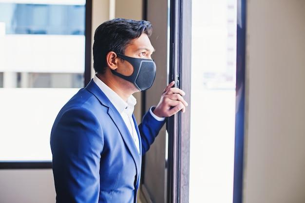 Indiase jonge man met gezichtsmasker kijkend uit het raam