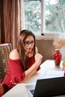 Indiase jonge vrouw die thuis studeert, webinar op laptop kijkt en in kladblok schrijft