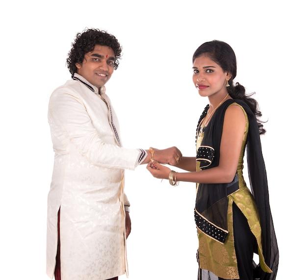 Indiase jonge zus die rakhi om de pols van zijn broer bindt, een traditie op het raksha bandhan-festival