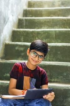 Indiase jongetje online studeren met behulp van mobiele telefoon thuis