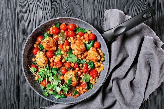 Indiase keuken: kikkererwten en kip curry van kippendijen zonder been met cherrytomaatjes en spinazie geserveerd met verse koriander op een koekenpan op een zwarte houten ondergrond, bovenaanzicht, close-up