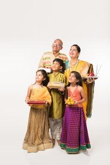 Indiase kinderen met grootouders in traditionele kleding met geschenken, snoep en puja of pooja thali of selfie te nemen, geïsoleerd op witte achtergrond